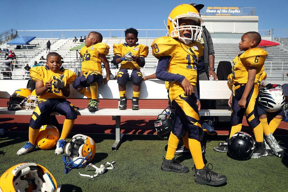 The Berkeley Jr. Bears Pop Warner Football Tiny Mites take a break after the first game during a football jamboree at Oak Grove High School in San Jose on Aug. 26. Photo: Scott Strazzante / The Chronicle