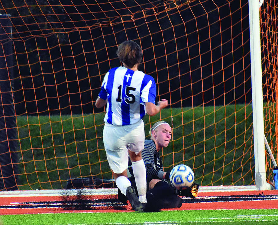 Edwardsville keeper Gabe Noll, right, kicks the ball away from Marquette's Trenton Dietiker early in the first half of Tuesday's non-conference game inside the District 7 Sports Complex. Photo: Matthew Kamp