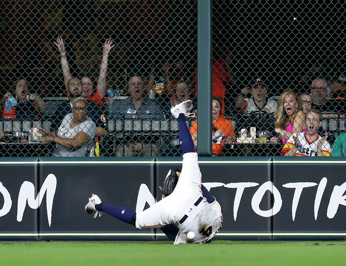 Houston Astros George Springer (4) tumbles after diving for Seattle Mariners Robinson Cano's double during the eighth inning of an MLB game at Minute Maid Park, Tuesday, September 18, 2018, in Houston.