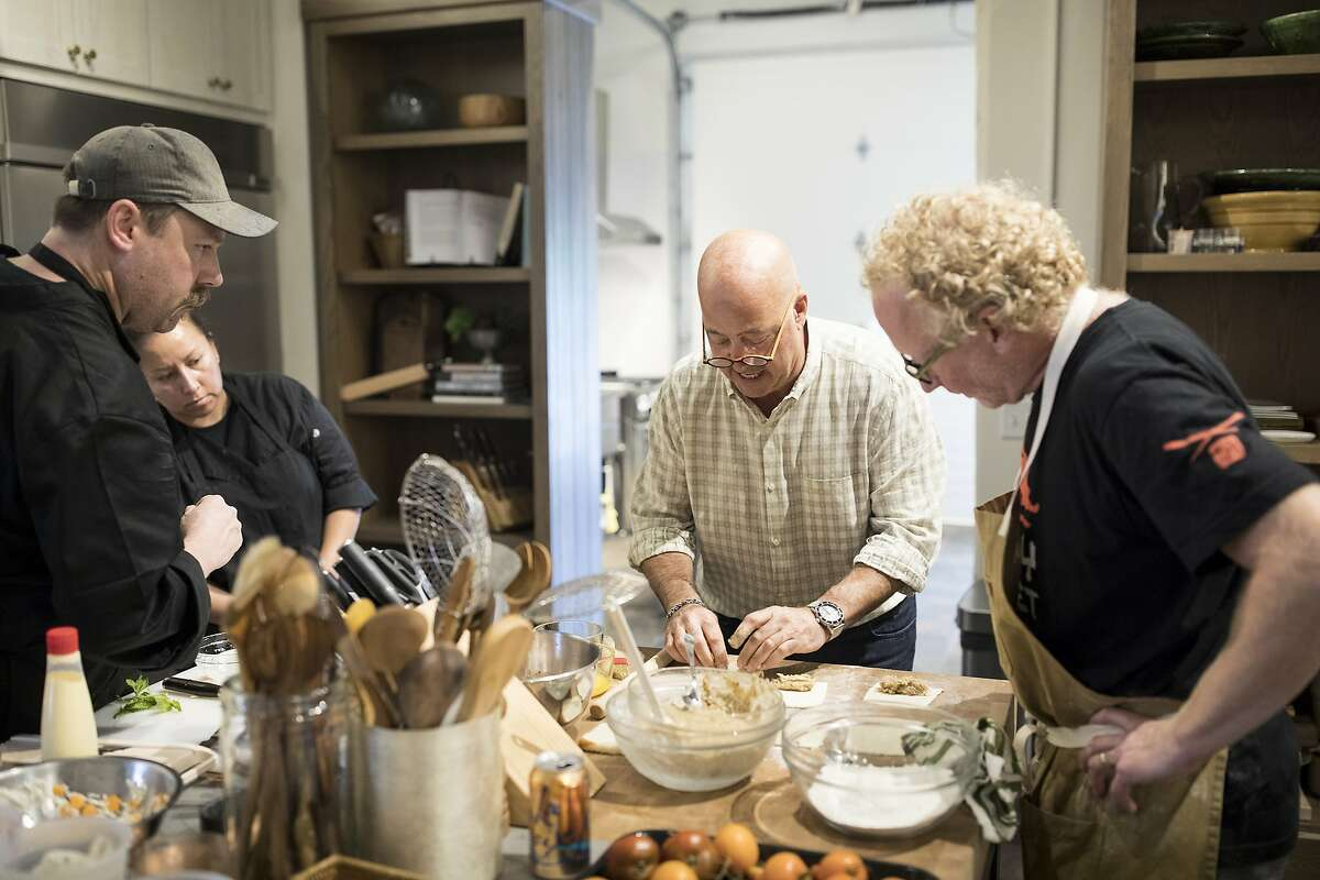 Andrew Zimmern, center, works with, from left, Jason Doyle, the executive chef at Lucky Cricket; Julietta Wences-Alcaide; and J.P. Samuelson on new recipes for the menu of his first restaurant, at his office in St. Louis Park, Minn., Aug. 15, 2018. Zimmern is apologizing for his comments about Chinese restaurants after he was criticized as culturally insensitive.