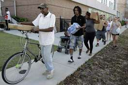 People walk away after receiving MREs, (Meals Ready To Eat) water and tarps at distribution area in Wilmington, N.C. Tuesday, Sept. 18, 2018. (AP Photo/Chuck Burton)