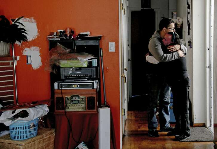 Mario Tello hugs his mother, Juana Ines Tello, as they pack up their belongings in their home of 18 years in San Francisco. The family is facing eviction, a battle they've been fighting for eight years.