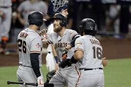San Francisco Giants' Hunter Pence, center, is greeted by teammates Aramis Garcia (16) and Chris Shaw (26) after hitting a two-run home run, while San Diego Padres catcher Austin Hedges, behind, waits during the second inning of a baseball game Tuesday, Sept. 18, 2018, in San Diego. (AP Photo/Gregory Bull)