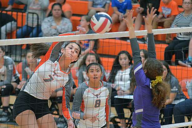 United teammates look on as Violetta Guerrero spikes the ball against an LBJ defender Tuesday, September 18, 2018 at the United High School Gym.