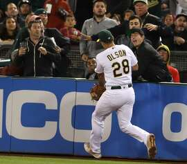 A fan catches a Los Angeles Angels' pop up in front of Oakland Athletics' Matt Olson in 3rd inning during MLB game at Oakland Coliseum in Oakland, Calif. on Tuesday, September 18, 2018.