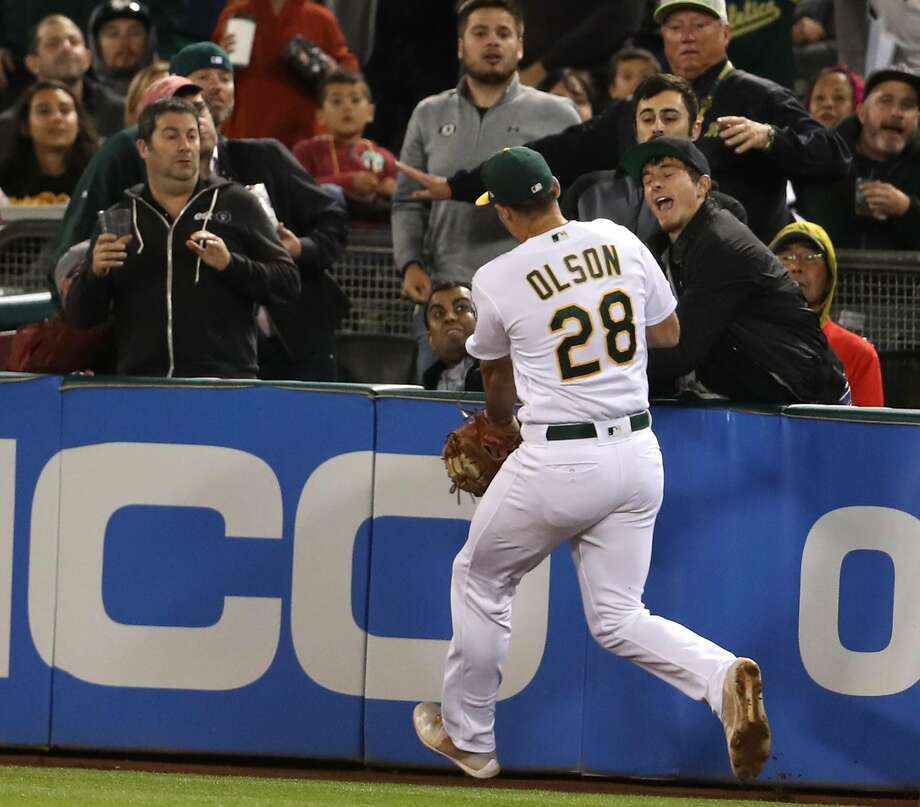 A fan catches a Los Angeles Angels' pop up in front of Oakland Athletics' Matt Olson in 3rd inning during MLB game at Oakland Coliseum in Oakland, Calif. on Tuesday, September 18, 2018. Photo: Scott Strazzante / The Chronicle