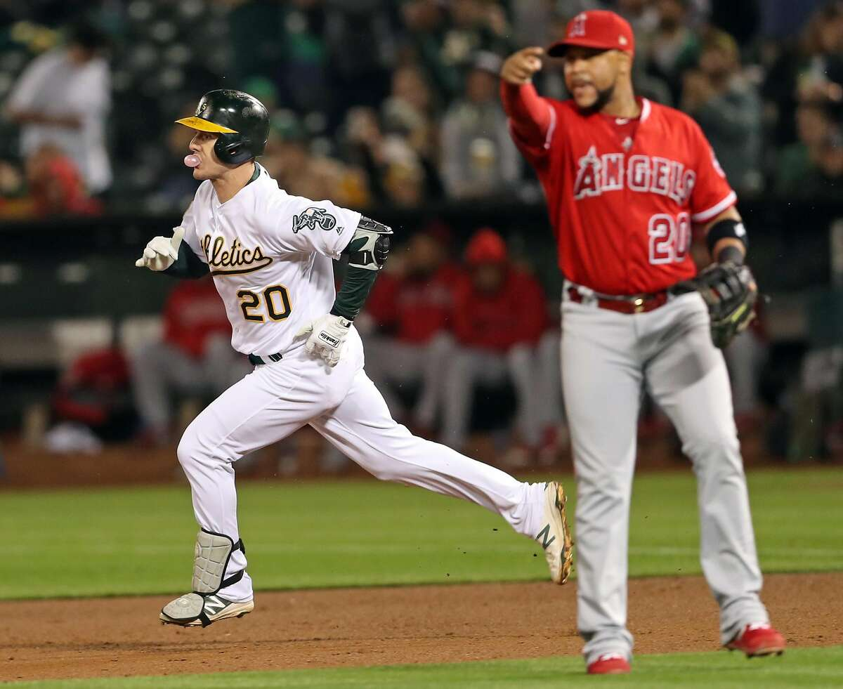 Oakland Athletics' Mark Canha blows a bubble while heading to second base during his 3-run double in 4th inning against Los Angeles Angels and Jose Fernandez (20) during MLB game at Oakland Coliseum in Oakland, Calif. on Tuesday, September 18, 2018.