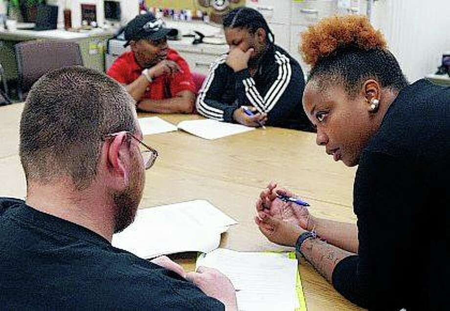 Administration counselor Karlesia Pickett assists Jonathan Sweet as he fills out paperwork along with Rakia Joyner and Khalilah Land during the monthly Job Corps orientation at Old King's Orchard Community Center in Decatur. Job Corps, a program administered by the U.S. Department of Labor, offers free education and vocational training. Photo: Jim Bowling | Herald & Review (AP)
