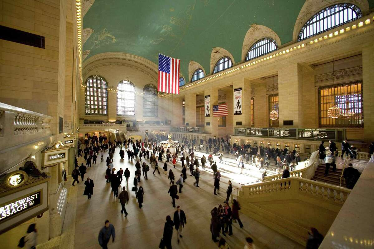 About 700,000 people visit, dine, shop or pass through Grand Central Terminal every day. A view from above showcases a popular meeting place the famous information booth with its gem of a clock, the astrological ceiling mural with its glittering stars, the Beaux Arts interior design and arched windows.