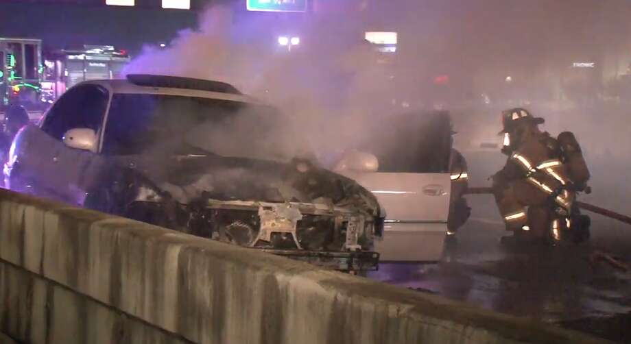 Firefighters extinguish a car that caught fire on the North Freeway near Crosstimbers on Tuesday, Sept. 18, 2018. Photo: Metro Video