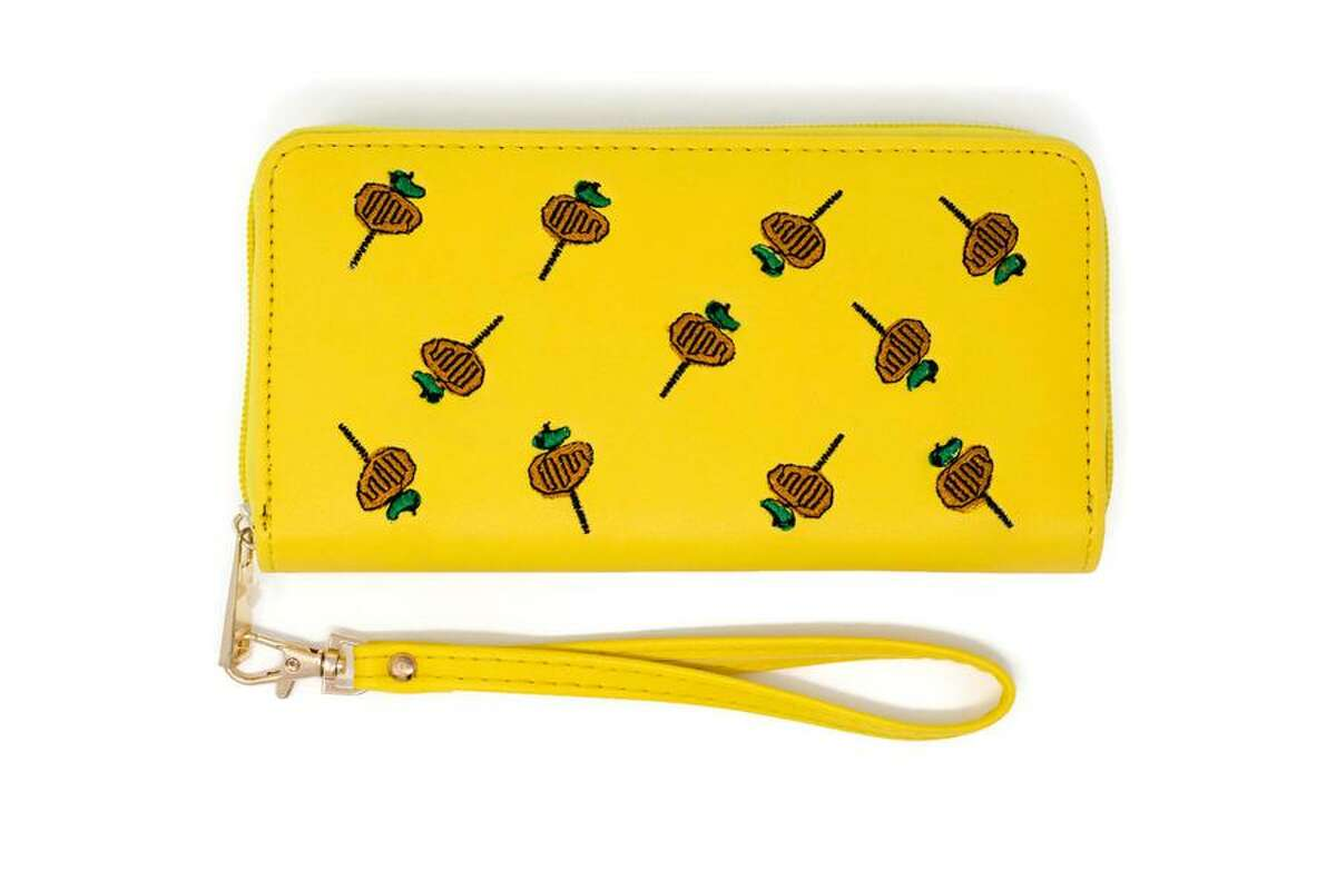 SA Flavor, a local company, launched the accessory Wednesday morning. The new wallet features 11 embroidered tiny chicken-on-a-sticks, plenty of space inside for cards, IDs and coupons and a wristlet to keep hands free to stack NIOSA cups and buy chicken-on-a-stick, of course.