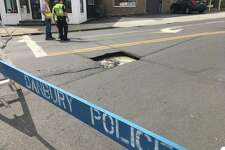 Danbury police officers stand near a sinkhole that opened Wednesday on Franklin Street.