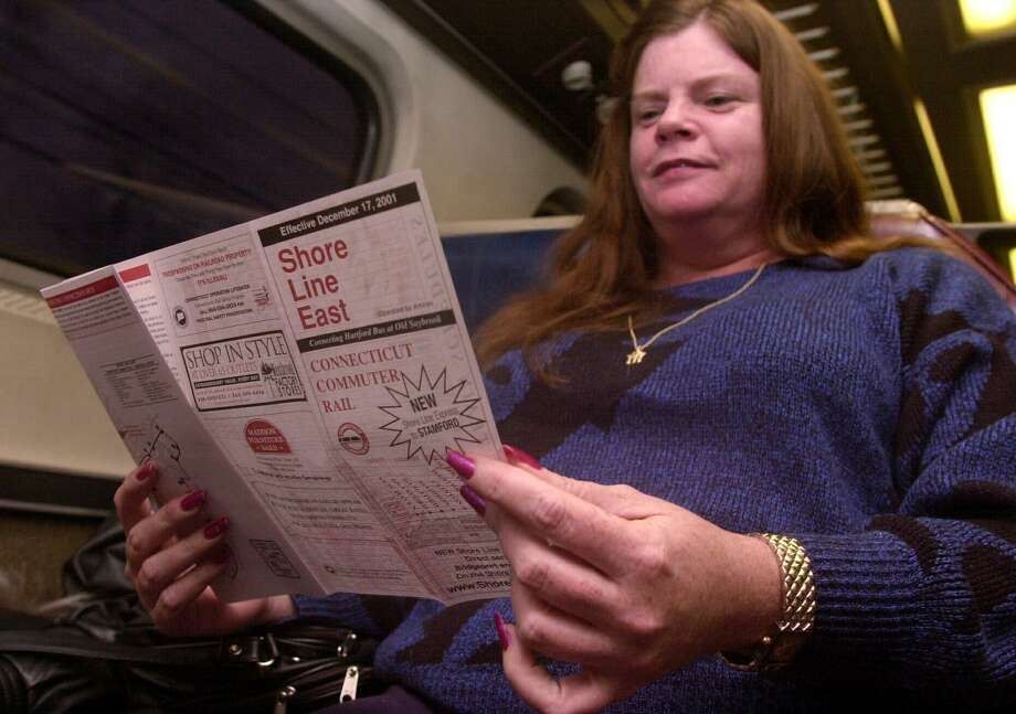 Stamford_010902_Ellie Traver reviews the Shore Line East schedule aboard the ShoreLine Express train from Stamford to New Haven. Kathleen O'Rourke/staff photo Photo: Kathleen O'Rourke / ST