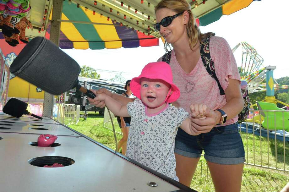 Sara Froehlich gets help from her mom Lexi as she plays Whac-A-Mole during the Wilton Rotary Club annual family carnival on Sunday September 16, 2018 in Wilton Conn. The event is a fundraiser that benefits the Wilton Rotary Club's community improvement projects both locally and internationally. Photo: Alex Von Kleydorff / Hearst Connecticut Media / Norwalk Hour