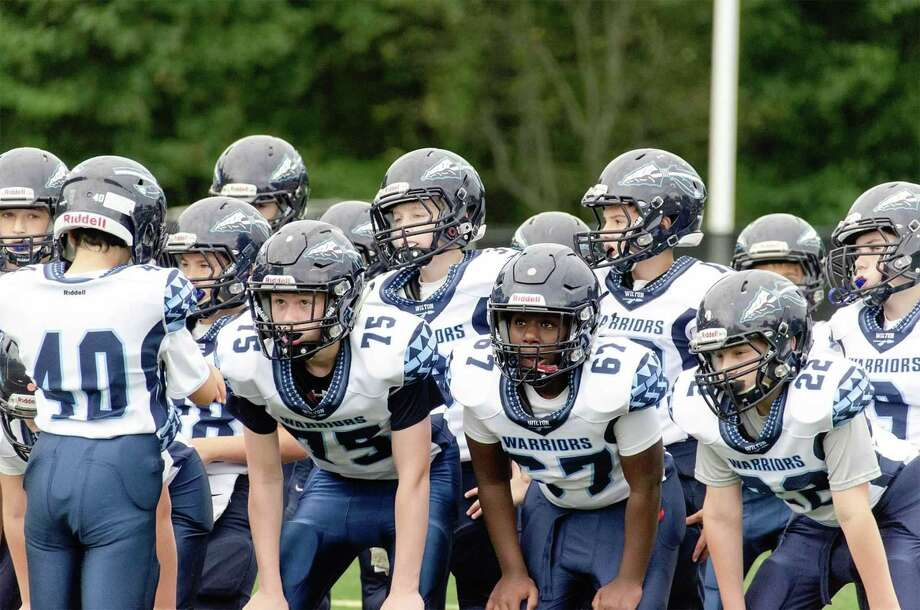 Members of the Wilton Sixth Grade Blue team, including Cole Siegel (75), Maja Driscoll (67) and Ryan Meenan (22), listen to their quarterback call the play during a game last week. Photo: Contributed Photo