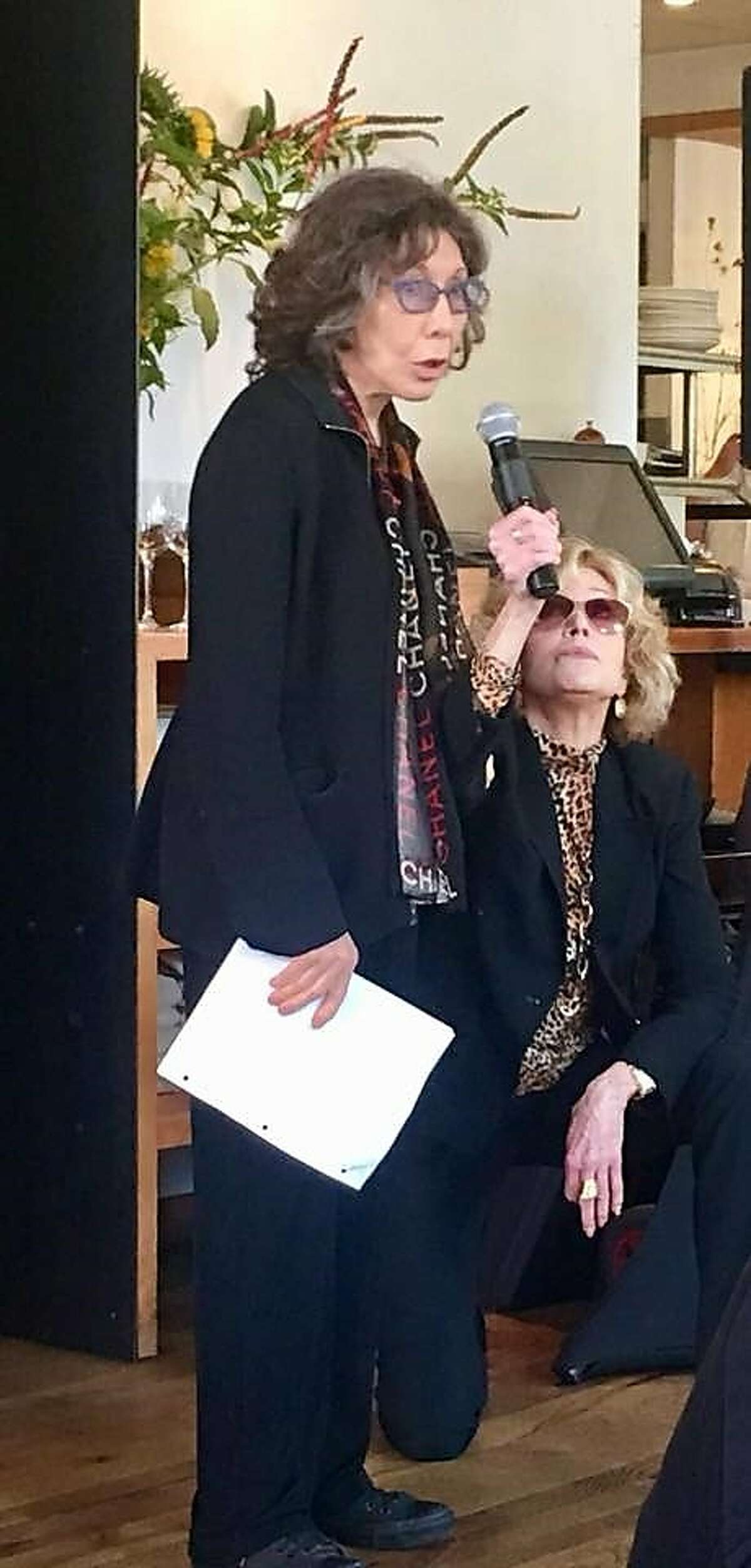 Jane Fonda holds a mic for Lily Tomlin at benefit for onefairwage.org