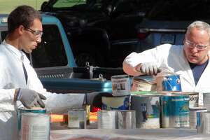 File photo of workers collecting used paint and stain cans at a hazardous waste collection.