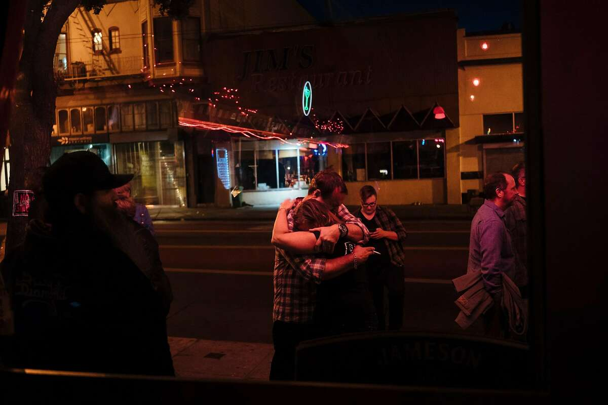Doc's Clock owners, Brian MacGregor and Carey Suckow embrace each other as friends and patrons celebrate the debut lighting of the bar's famous sign in San Francisco, Calif., on Tuesday, Sept. 18, 2018.