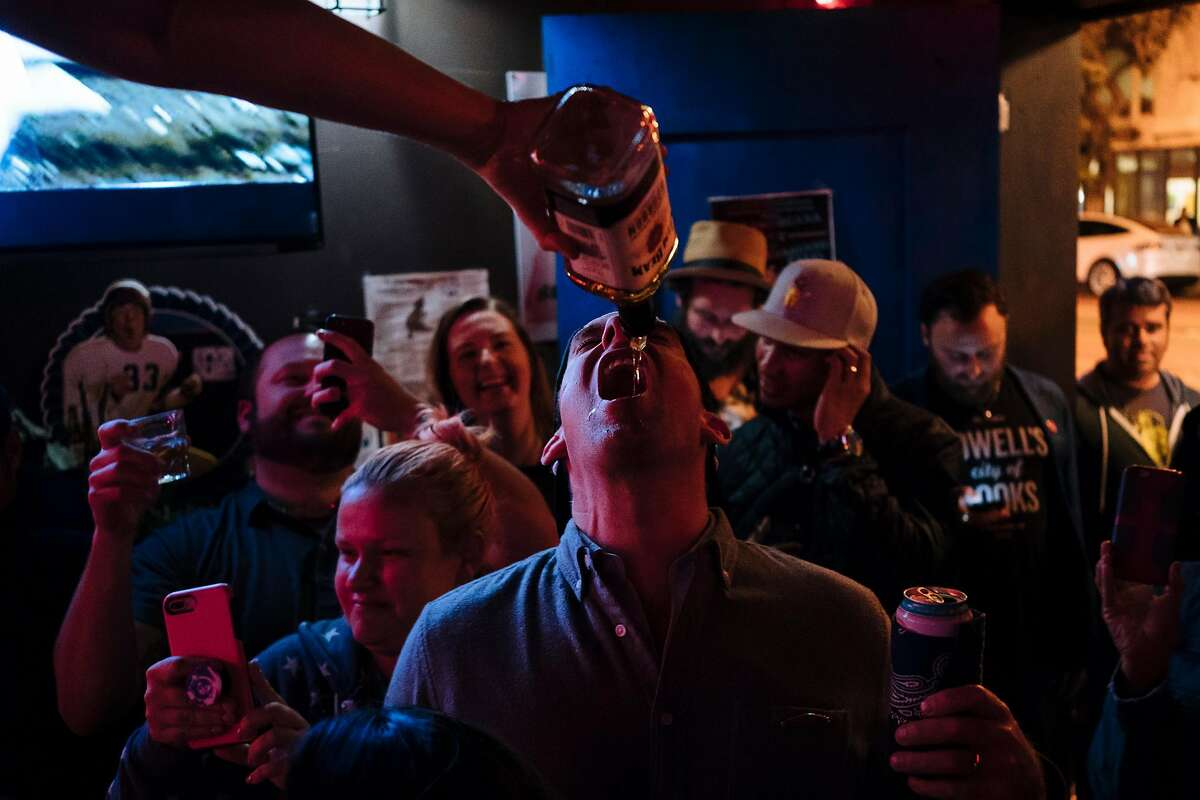 Jack Choate takes a free shot from Carey Suckow as patrons celebrate the return of Doc's Clock's famous neon sign in San Francisco, Calif., on Tuesday, Sept. 18, 2018.