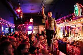 Brian MacGregor raises his glass for a toast to congratulate his wife, Carey Suckow, for the return of Doc's Clock's famous neon sign in San Francisco, Calif., on Tuesday, Sept. 18, 2018.