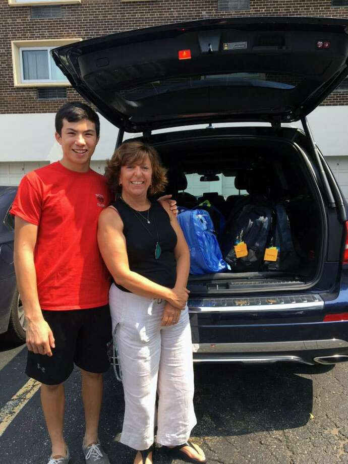Service League of Boys member Justin Weitfieldt and Lisa Habasinski, of the Family & Childrens Agency, kick off the new SLOBs philanthropic year by donating school backpacks to those in need. Photo: Contributed Photo