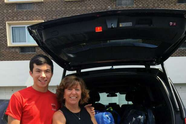 Service League of Boys member Justin Weitfieldt and Lisa Habasinski, of the Family & Childrens Agency, kick off the new SLOBs philanthropic year by donating school backpacks to those in need.