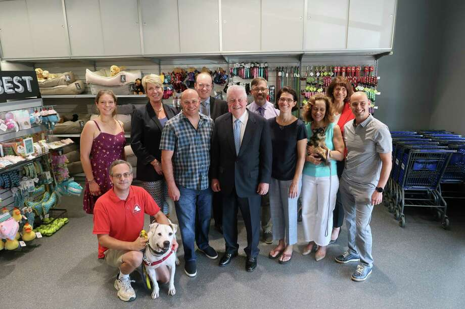 """Back row, from left, Adopt-A-Dog Executive Director Kristen Alouisa, state Rep. Laura Devlin, Kevin Caskin of People's United Bank, Director of Community and Economic Development Mark Barnhart and Fairfield Chamber of Commerce President Beverly Balaz. Front row, from left, Adopt-a-Dog staff member Brian Gordiski, Pet Pantry co-owner Ari Jacobson, First Selectman Michael Tetreau, state Rep. Cristin McCarthy Vahey, Giulia Tetreau, and Pet Pantry co-owner Adam Jacobson. On Sept 5., Pet Pantry hosted the firstsSelectman, town legislators and the Chamber of Commerce to a """"ribbon chewing"""" ceremony with an Adopt-a-Dog event."""