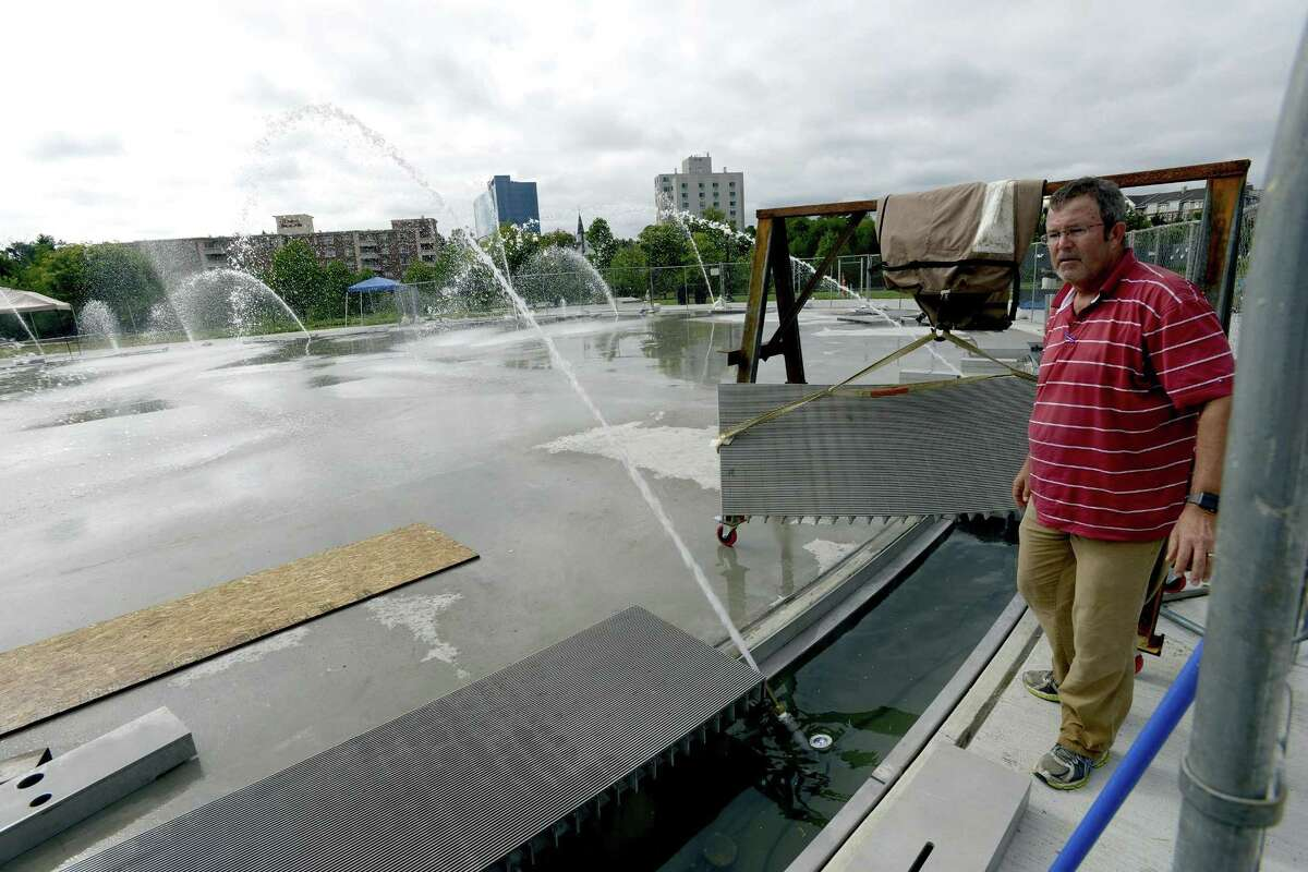 Scott Johnston, co-owner of Delta Fountains, tests one of six zones of the new fountain set to open Thursday at Mill River Park.