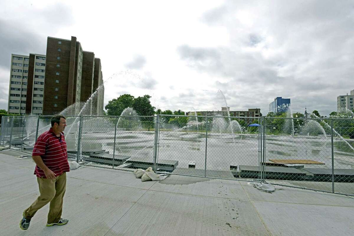 Scott Johnston, Co-Owner of Delta Fountians, Jacksonville, Florida tests one of six zones of the new fountain at Mill River Park. The fountain, which will also serve as an ice rink in the winter, is schedule to open next week. Johnston's company also help design the fountains at the World Trade Center memorial.