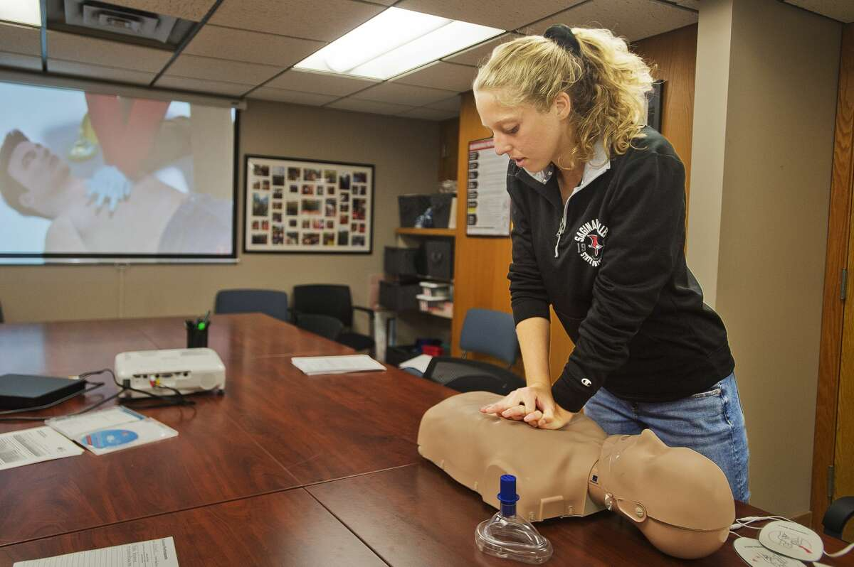 Saginaw Valley State University student Rylea Grassmid, 19, practices giving chest compressions during a CPR training session on Wednesday, Sept. 19, 2018 at Independent Community Living in downtown Midland. (Katy Kildee/kkildee@mdn.net)