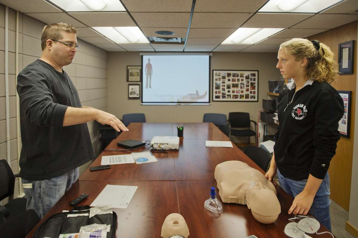 CPR Instructor Jeremy Tomczak, left, walks Saginaw Valley State University student Rylea Grassmid, 19, right, through a CPR training session on Wednesday, Sept. 19, 2018 at Independent Community Living. (Katy Kildee/kkildee@mdn.net)