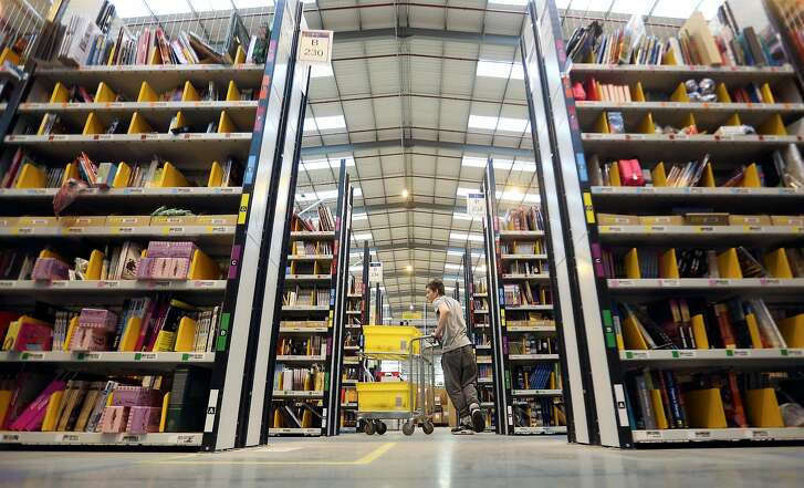An employee pushes a cart between racks of books and merchandise as he processes customer orders ahead of shipping at one of Amazon.com Inc.'s fulfillment centers in Peterborough, U.K., on Tuesday, Nov. 25, 2014. Online spending will account for about 13 percent of December sales, up from 12 percent a year earlier, according to forecasters at Deloitte LLP. Photographer: Chris Ratcliffe/Bloomberg