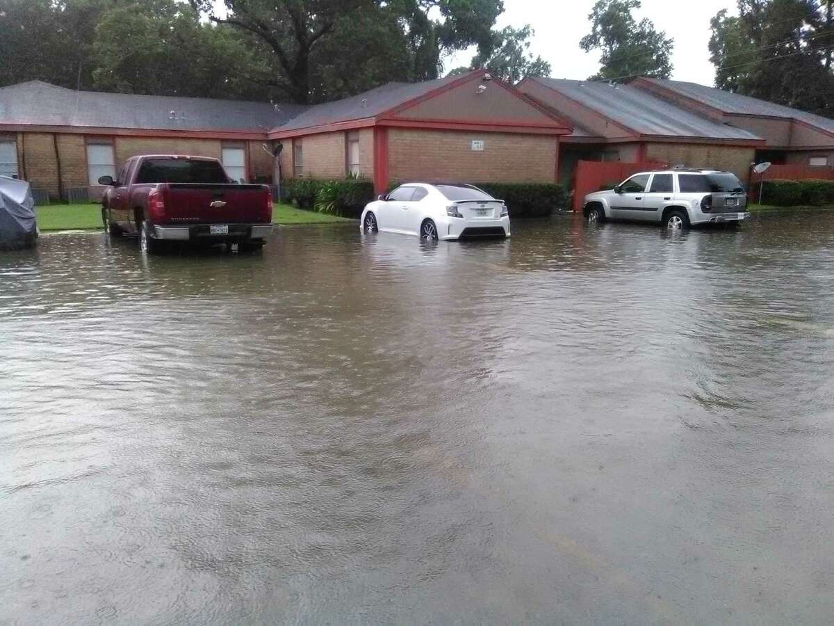 A Huffman area residential complex experiences knee-deep standing water in parking lot Aug. 27. Flood waters continue to rise.