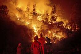 FILE - In this Aug. 7, 2018 file photo, firefighters monitor a backfire while battling the Ranch Fire, part of the Mendocino Complex Fire near Ladoga, Calif. The U.S. Forest Service says the largest wildfire in California history is now 100 percent contained. The service said Wednesday, Sept. 19, 2018, the Mendocino Complex, twin fires that erupted in July in Lake County, scorched 720 square miles (1,865 square kilometers) of brush and timber north of San Francisco, destroyed 157 homes and killed a firefighter. (AP Photo/Noah Berger, File)