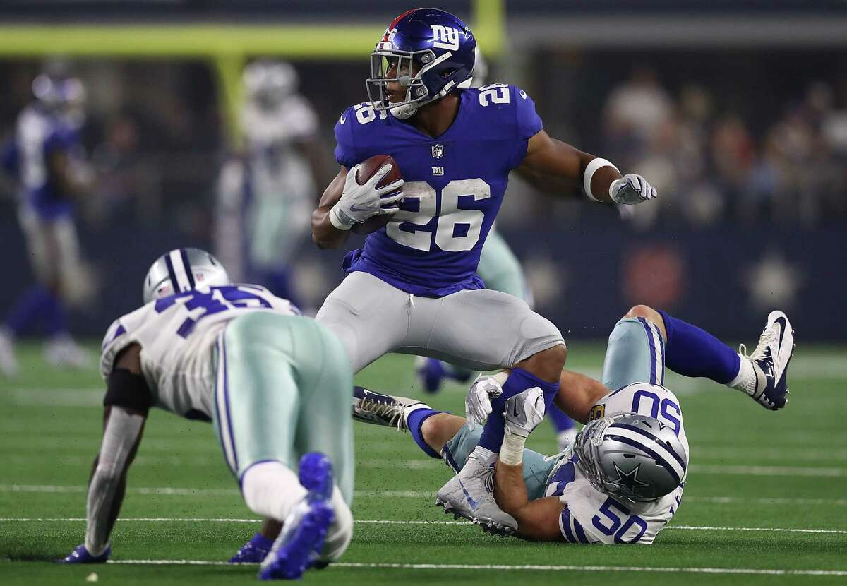 ARLINGTON, TX - SEPTEMBER 16: Saquon Barkley #26 of the New York Giants is tackled by Sean Lee #50 of the Dallas Cowboys in the second quarter at AT&T Stadium on September 16, 2018 in Arlington, Texas.