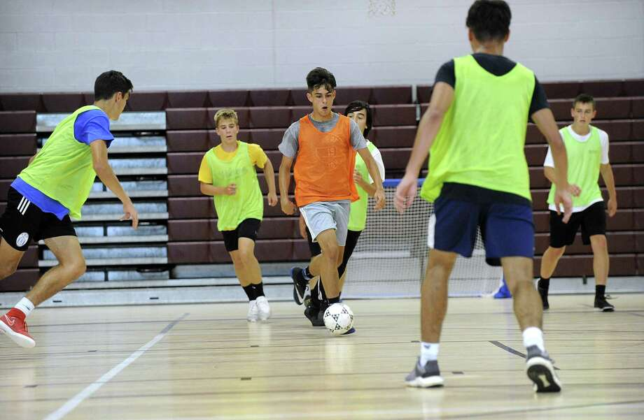 The boys varsity and junior varsity soccer teams at Bethel High School practice in the school gym Tuesday, Sept. 18, 2018. Without a turf field, teams are forced to cancel practice or practice inside on rainy days. Photo: Carol Kaliff / Hearst Connecticut Media / The News-Times