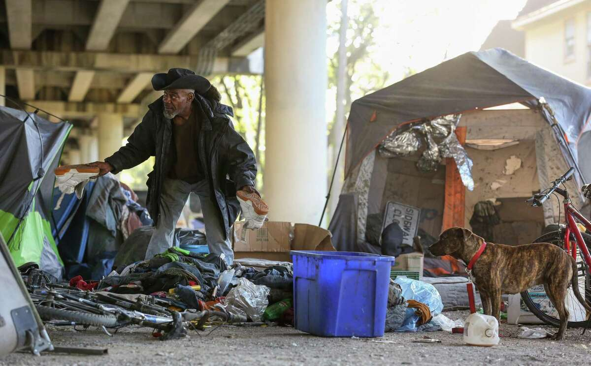 A man known as Trampus finds a pair of shoes he wishes to keep while sorting through his belongings, before city contractors conduct a cleanup of the Wheeler Homeless Encampment located under the US 59 Freeway in Houston.