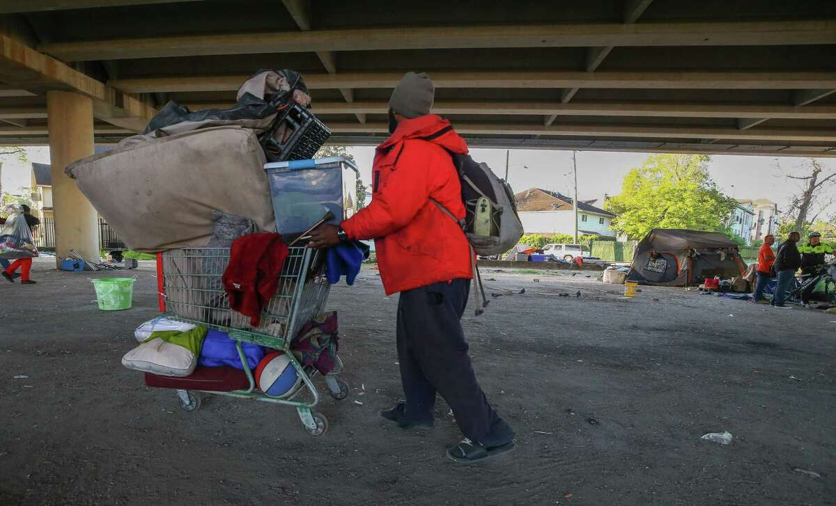 A man moves his belongings as city contractors conduct a cleanup of the Wheeler Homeless Encampment located under the US 59 Freeway in Houston.