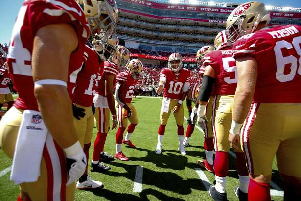 49ers' quarterback Jimmy Garoppolo gathers the offense around during practice prior to Sunday's game against the Lions at Levi's Stadium.