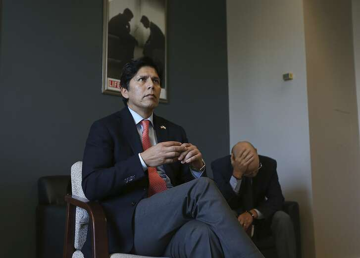 State Sen. Kevin de Leon, D-Los Angeles, accompanied by Dan Reeves, his chief of staff, sits in his office and watches as his renewable energy bill, did not immediately receive enough votes for passage, Tuesday, Aug. 28, 2018, in Sacramento, Calif. The bill, which would require the state to generate 60 percent of its energy from renewable sources by 2030 and set a goal of phasing out fossil fuels by 2045, was put on call for a later vote. (AP Photo/Rich Pedroncelli)