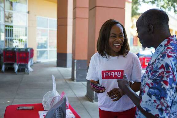 "Tolulope Aladejobi, a Rebtel ""activist,"" the term the company uses for their on-the-street sales representatives, helps Waidi Shodimu load credits onto his Rebtel app, Wednesday, Aug. 22, 2018 in Houston. Shodimu, who has been living in the United States for 35 year, recently started useing the app to call family in Nigeria. He used to buy phone cards for international calls, but he has found the app more convenient, he said. Shodimu is a regular customer of Aladejobi. He will even leave his phone and credit card with her when he goes in to shop at the Southwest Farmers Market. Rebtel is a Swedish company that has a phone application allowing affordable international calling and soon will be able to transfer money internationally."