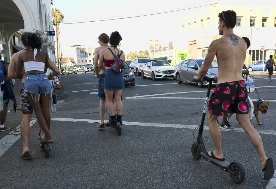 FILE - In this July 24, 2018, file photo, riders make their way across a street on Bird electric scooters in the Venice Beach section of Los Angeles. Californians could ride motorized scooters without helmets under legislation headed to Gov. Jerry Brown. Lawmakers in the California Assembly passed the bill Wednesday, Aug. 29, 2018. It would let adults ride the devices without helmets and allow riders to travel on faster-moving streets.  Photo: Richard Vogel / Associated Press
