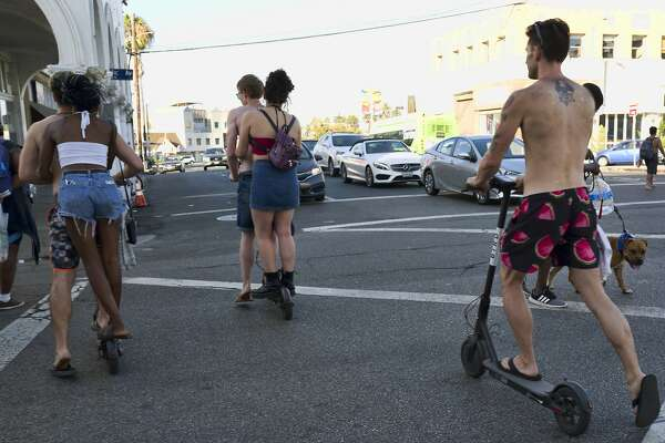 FILE - In this July 24, 2018, file photo, riders make their way across a street on Bird electric scooters in the Venice Beach section of Los Angeles. Californians could ride motorized scooters without helmets under legislation headed to Gov. Jerry Brown. Lawmakers in the California Assembly passed the bill Wednesday, Aug. 29, 2018. It would let adults ride the devices without helmets and allow riders to travel on faster-moving streets. (AP Photo/Richard Vogel, File)