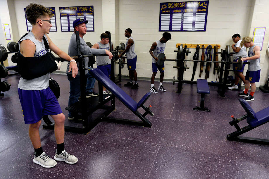 Austin Smith watches as his teammates on the Sabine Pass football team lift weights on Wednesday afternoon. Smith is out with a possible broken wrist. 