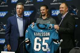 San Jose Sharks general manager Doug Wilson, left, newly acquired defenseman Erik Karlsson, center, and coach Peter DeBoer, right, pose with a jersey during a news conference in San Jose, Calif., Wednesday, Sept. 19, 2018. (AP Photo/Josie Lepe)