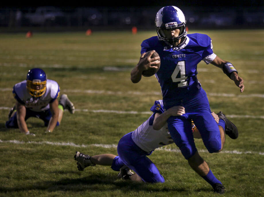 Coleman's Truman Webb carries the ball in a game against Ashley at the Comets' field last October. Ashley has since joined the growing ranks of schools opting to compete at the 8-man level, while Coleman is considering the possibility of someday doing the same. Photo: Daily News File Photo