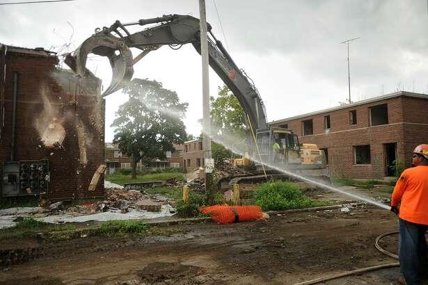 A worker sprays water to keep dust down during demolition at Marina Village in Bridgeport.