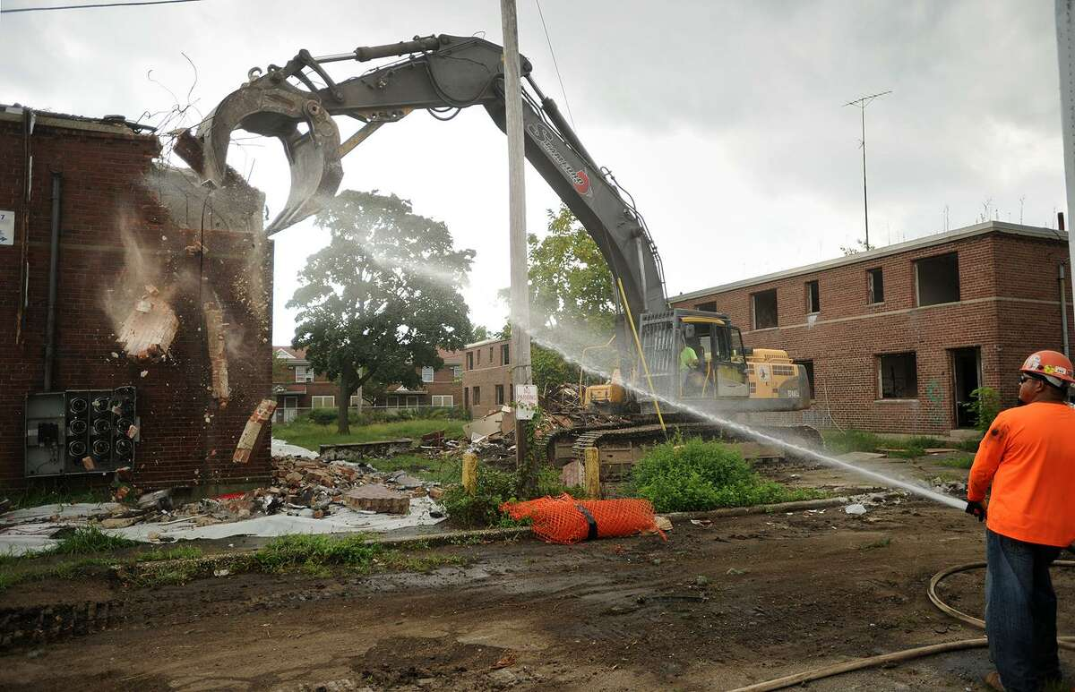 A worker sprays water to keep dust down during demolition at Marina Village in Bridgeport.