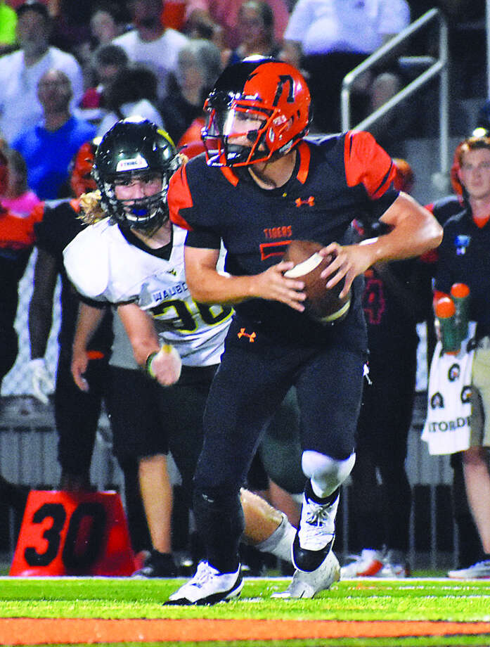 Edwardsville quarterback Luke Oglesby looks down the field as he tries to avoid the rush. Photo: Matthew Kamp