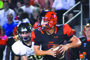 Edwardsville quarterback Luke Oglesby looks down the field as he tries to avoid the rush.